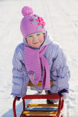 Warmly dressed smiling girl in pink scarf and hat relies on sled