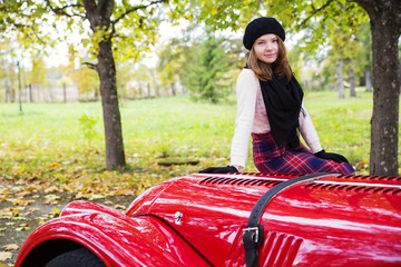 Woman in skirt on red car cowling