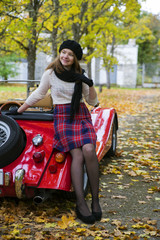 Woman in skirt posing on car back