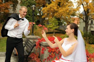 Piękna młoda para bawi się kolorowymi jesiennymi liśćmi.
