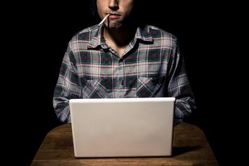 Cigarette smoking man working on laptop