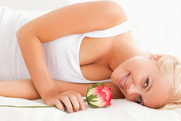Close up of a smiling woman with a rose