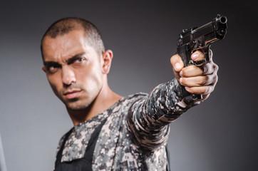 Soldier with guns against dark background