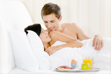 Lying man serves woman breakfast in bed-room