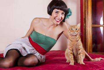 pin-up girl with short hair in bed with a cute cat.