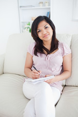 Woman holding a notebook while sitting in a couch