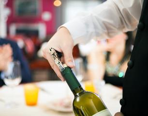Waiter uncorking wine
