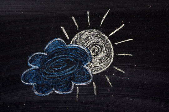 Chalk drawing of the sun and a cloud with a silver lining