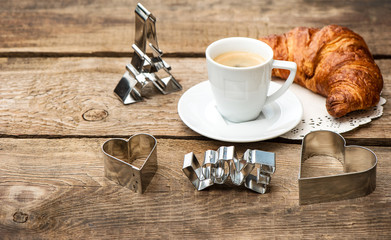 Cup of black coffee with croissant and heart decoration