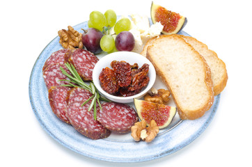 plate of snacks - sausage, bread, figs, grapes, nuts