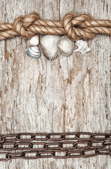 Metal chain, ship rope and seashells on the old wood