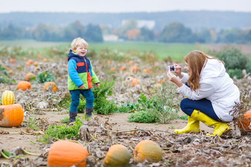 Young mother making picture of her son on pumpkin field.