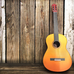 Acoustic wooden guitar leaning on a wooden fence.