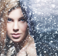 Beauty portrait of a young woman on a snowy background