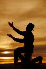 Fototapete - cowboy kneel silhouette both hands up
