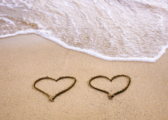 Symbols of two hearts drawn on sand, love concept