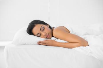 Calm sleeping woman lying on her bed