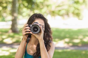 Front view of cute brunette woman taking a picture with her came