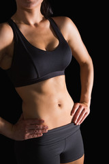 Mid section of slender fit woman posing in sportswear