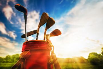 Golf equipment. Professional golf clubs at sunset