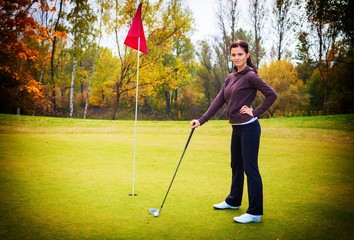 Smiling woman golf player training on green