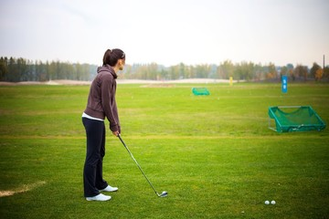 Young woman training golf at the driving range