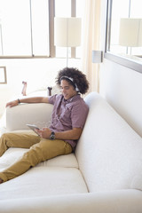 Young man wearing headphones and using digital tablet on sofa in living room