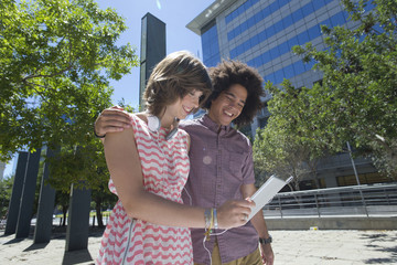 Smiling young couple using digital tablet in city