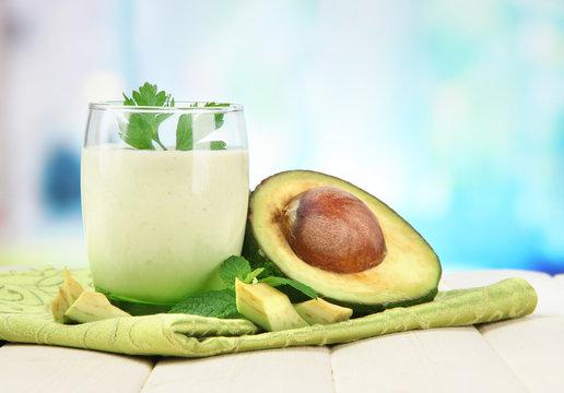Fresh avocado smoothie on bright background