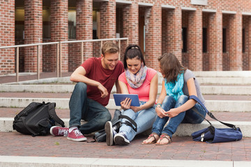 Smiling students sitting on stairs using tablet