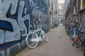 bicycle leaned against griffiti covered wall in amsterdam