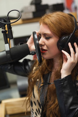 Concentrating beautiful singer recording a song