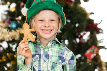 Elf boy holding gingerbread man