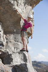 Portrait of confident female rock climber ascending rock face