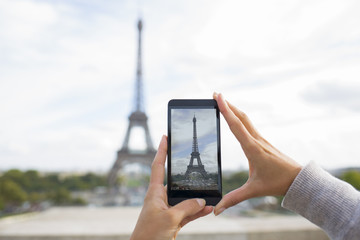 Woman taking pictures in front of Eiffel Tower, cell phone