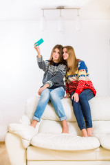 Two beautiful girls with a mobile phone