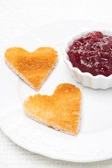 toasted bread in the shape of heart with berry jam, close-up