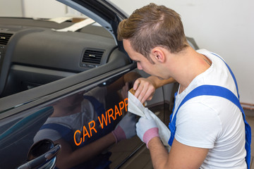 Car branding specialist puts logo with car wrapping film on auto