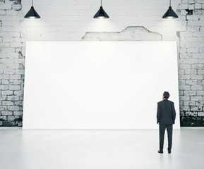 Man looking at white poster
