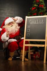 Santa Claus sitting near chalkboard