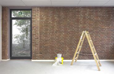 Malerarbeiten Leiter rmit Farbeimer vor Backsteinwand