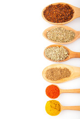 Spices in spoons on white