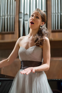 Beautiful opera singer sings in the concert hall