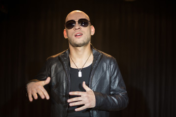 man in leather jacket with sunglasses gesturing