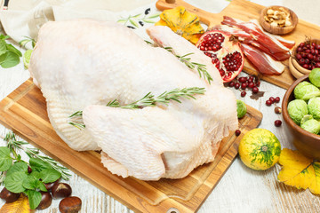 Whole raw  turkey on wooden cutting board and ingredients