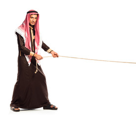 Young Arab pulling a rope isolated on white