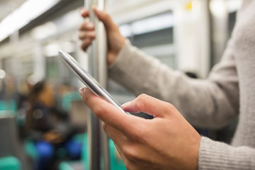 Woman using her cell phone in Subway, sms, e-mail, message