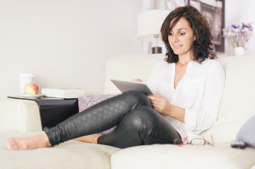 woman using tablet while resting on the sofa