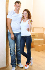 Young couple with keys to your new home on room background