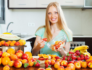 Smiling   woman cooking fruit salad